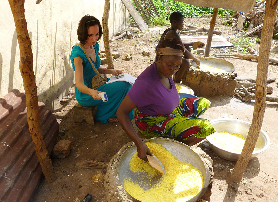 Lady roasting gari from yellow cassava in Tyo-Mu, Benue State, Nigeria and researcher Aurelie Bechoff recording temperature using infra-red thermometer.